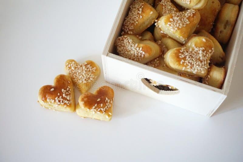 Les biscuits de sésame dans la forme du coeur, appartement s'étendent sur le fond blanc image stock