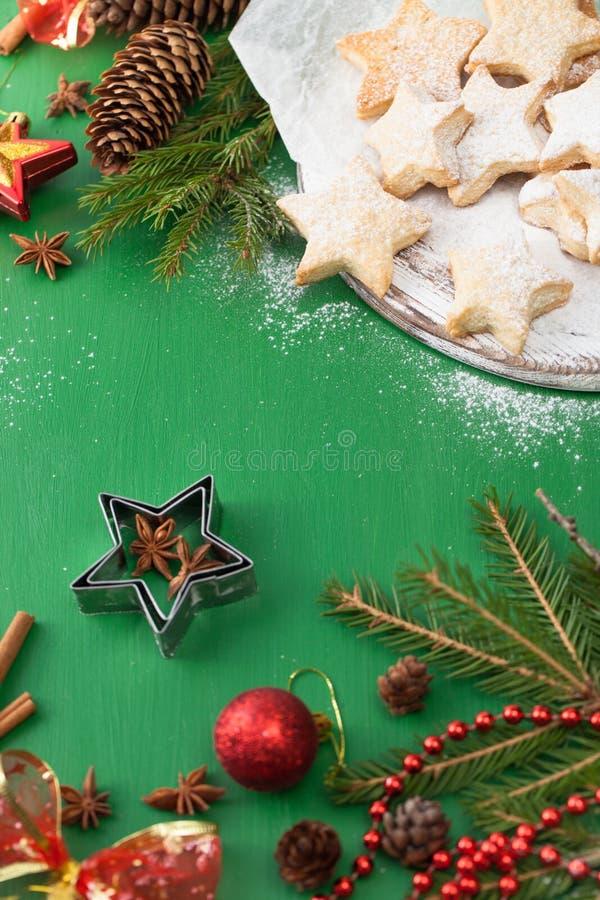 Les biscuits ont épousseté avec du sucre en poudre avec des décorations de Noël sur le vert images stock
