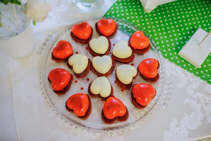 Les biscuits rouges et blancs de Valentine avec le coeur forment image libre de droits