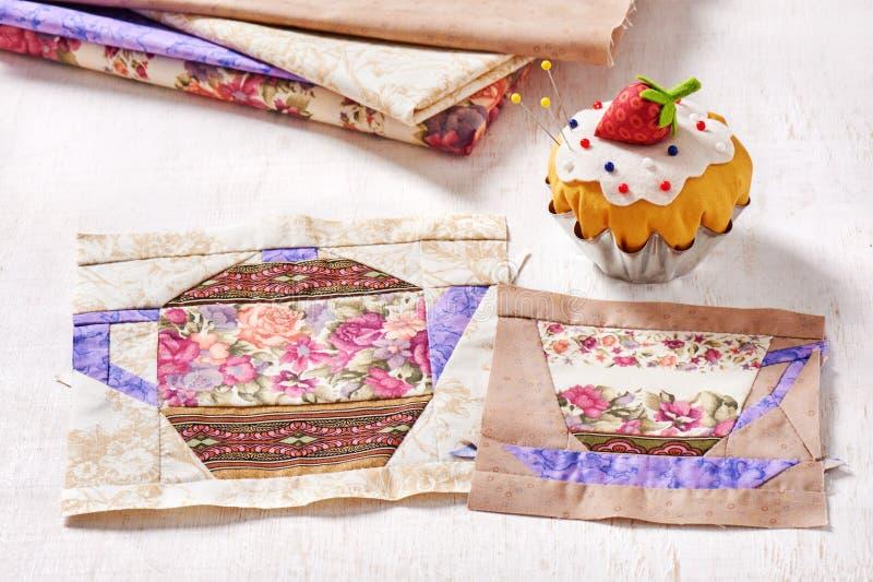 Les blocs de patchwork de la tasse et de la théière avec un modèle des fleurs et le coussin de goupille aiment un petit gâteau av images libres de droits
