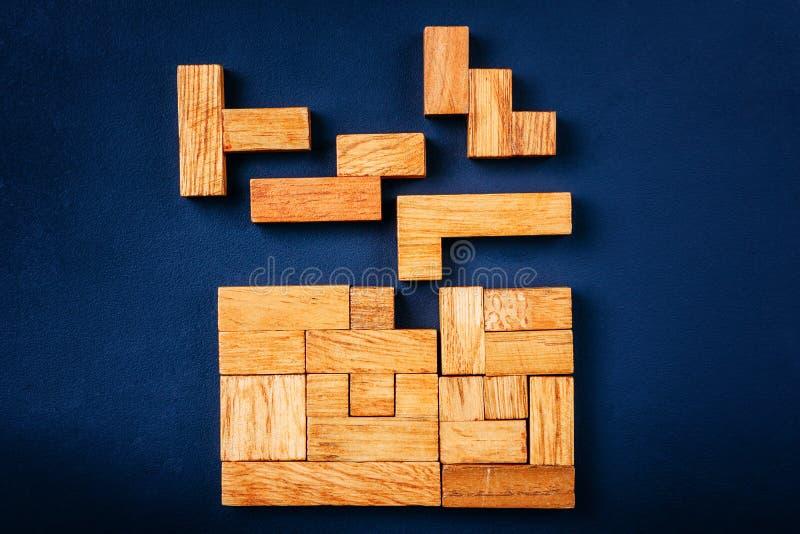 Les blocs en bois de différentes formes géométriques arrangent dans le chiffre solide sur un fond foncé Concept de solution de pe photos libres de droits