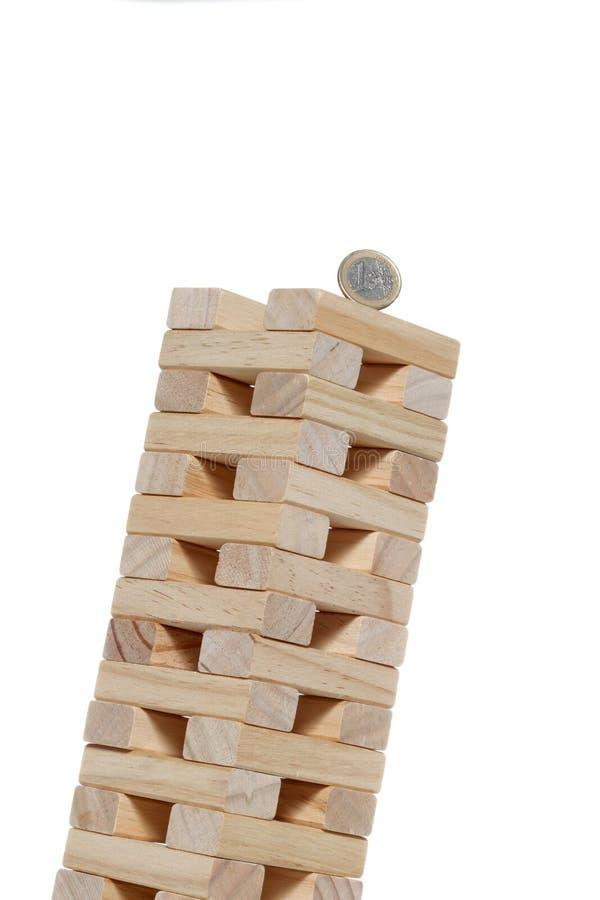 Les blocs en bois de jouet dominent avec une 1 pièce de monnaie d'euro sur le dessus incliné jusqu'à la chute d'isolement sur le  photo stock