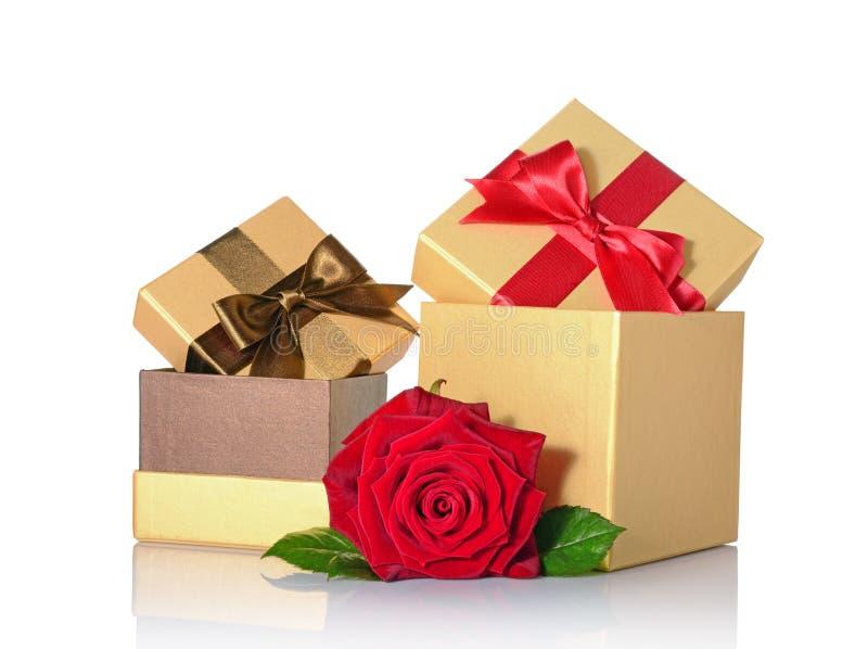 Les boîte-cadeau brillants classiques d'or avec les arcs bruns et rouges de satin et se sont levés image stock