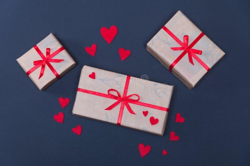 Les boîte-cadeau décorés des rubans rouges avec des arcs se trouvent sur un fond noir image libre de droits