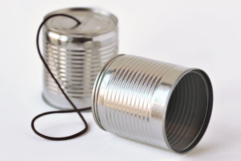 Les boîtes en fer blanc téléphonent sur le fond blanc - concept de communication photo stock
