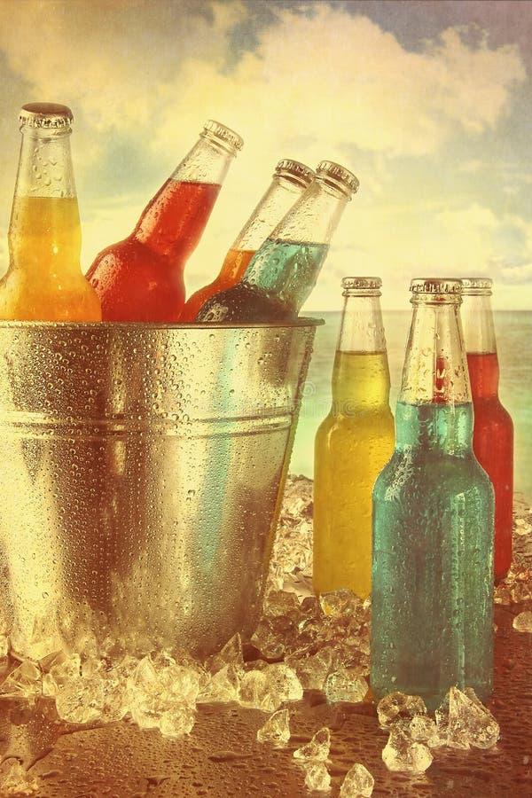 Les boissons d'été dans le seau à glace à la plage avec le vintage regardent photo stock