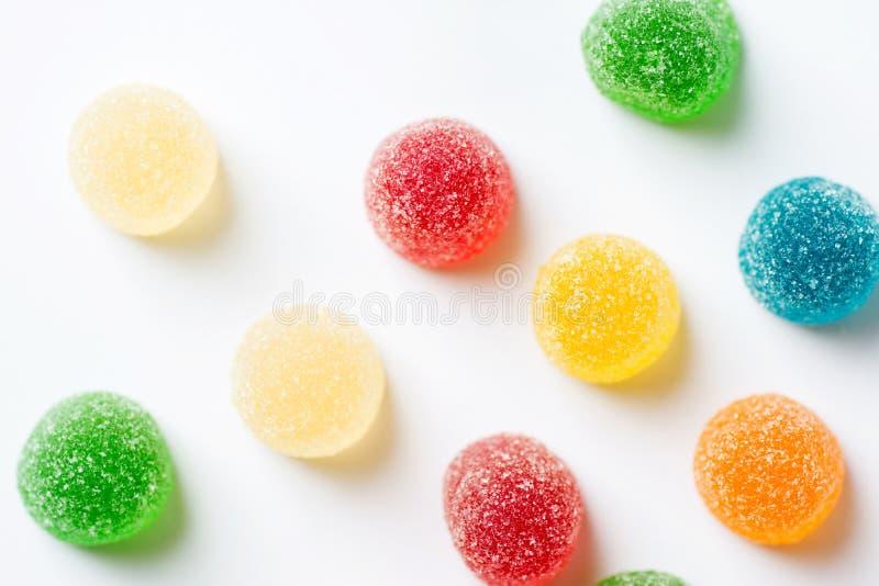 Les bonbons jaunes jaunes rouges oranges vertes pour la gelée sont enduits de sucre sur fond blanc Fête d'anniversaire des enfant images libres de droits