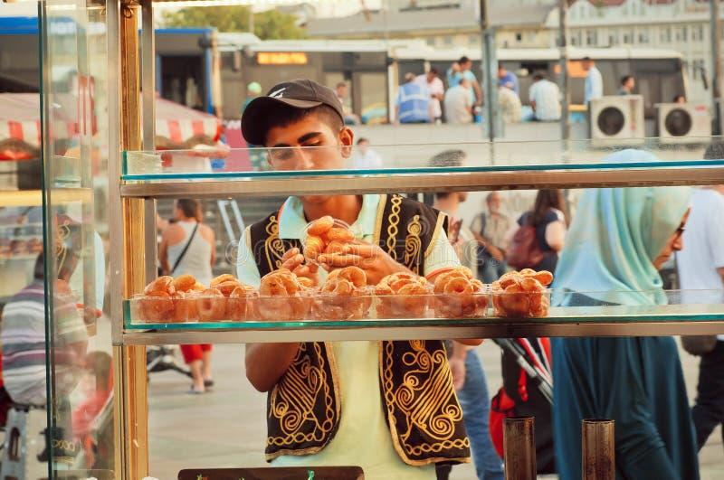 Les bonbons sur la nourriture de rue calent avec le vendeur dans les vêtements turcs traditionnels image libre de droits