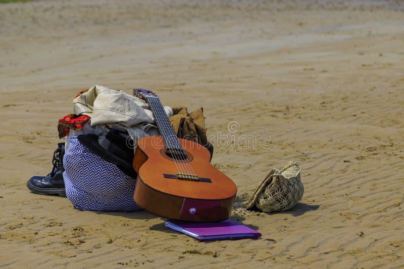Les bottes de guitare mettent en sac sur la plage images libres de droits