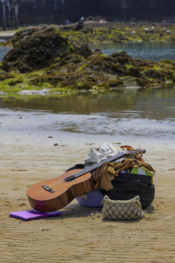 Les bottes de guitare mettent en sac sur la plage photographie stock libre de droits