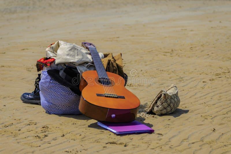 Les bottes de guitare mettent en sac sur la plage image libre de droits