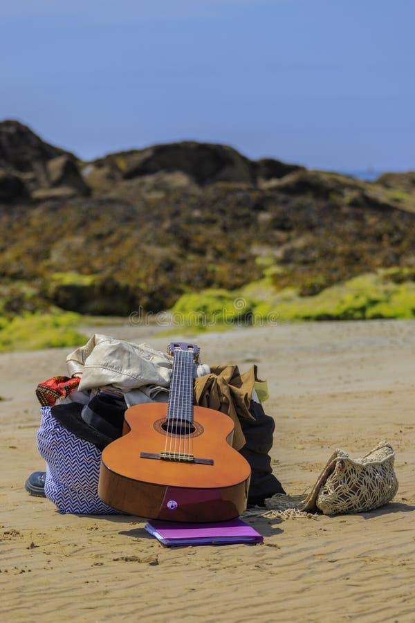 Les bottes de guitare mettent en sac sur la plage images stock