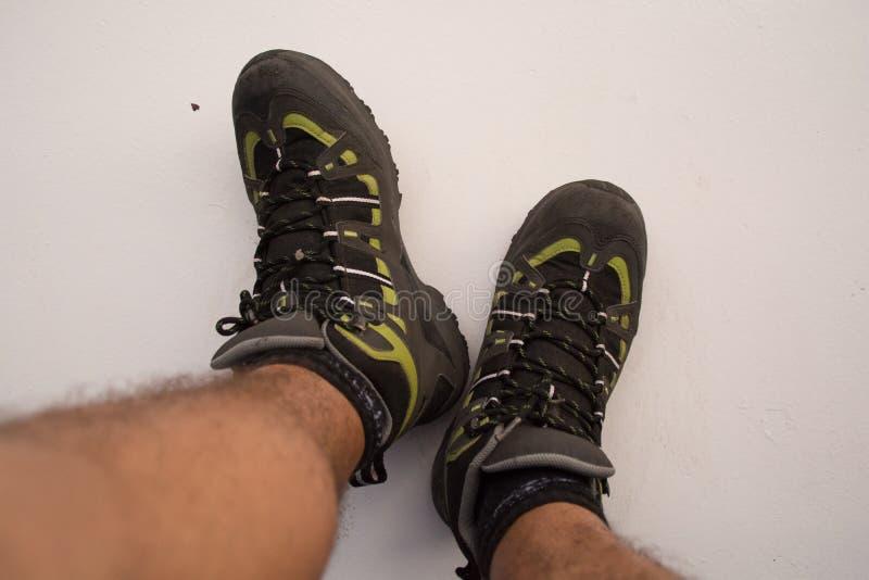 Les bottes de randonnée, bien usées et boueuses, isolées en blanc images stock
