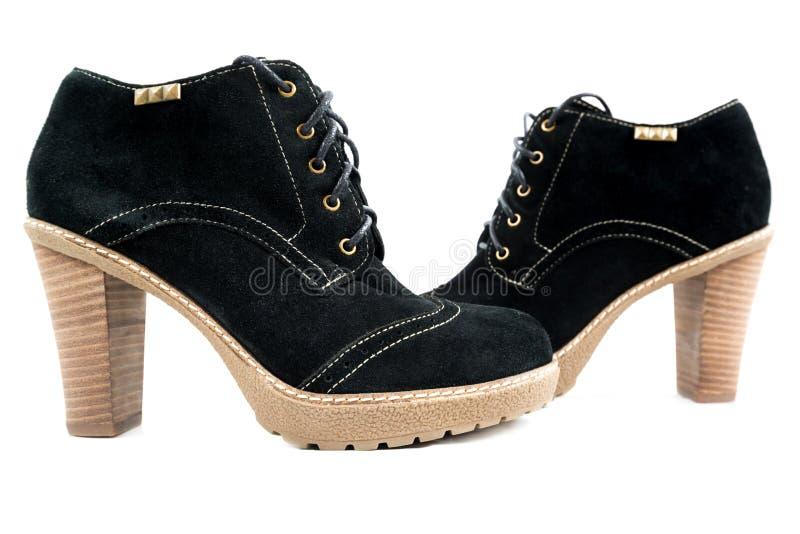 Les bottes des femmes avec le suède noir sur le fond blanc image stock