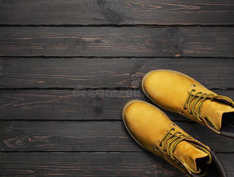 Les bottes du travail d'hommes jaunes du cuir naturel de nubuck sur l'appartement en bois foncé de vue supérieure de fond s'étend image libre de droits
