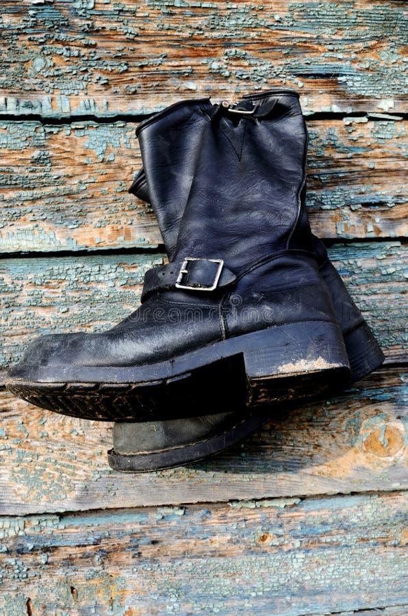 Les bottes en cuir de vieux vintage accrochent sur le mur image libre de droits