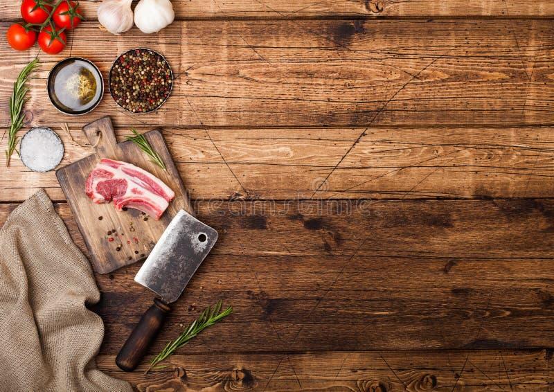 Les bouchers crus frais agnellent des côtelettes de boeuf sur le hachoir avec la cognée de viande de cru sur le fond en bois Sel, photo stock