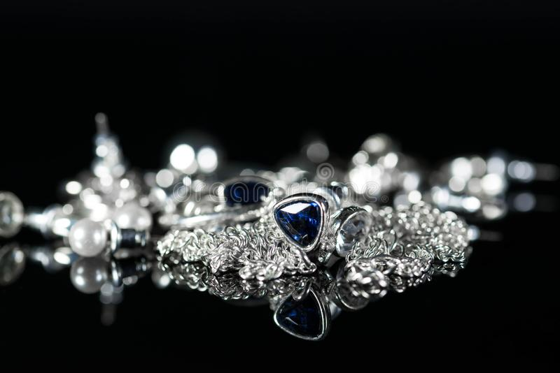 Les boucles d'oreille argentées de bijoux, chaîne, anneaux se ferment vers le haut du tir photographie stock