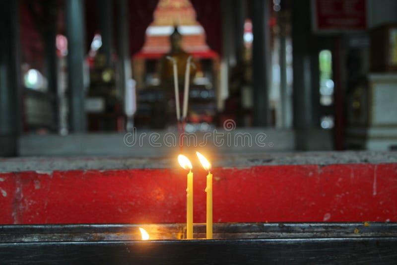 Les bouddhistes font le mérite, plaçant une bougie allumée et ont allumé l'encens avec le cadre de bougies sur l'autel de Bouddha images libres de droits