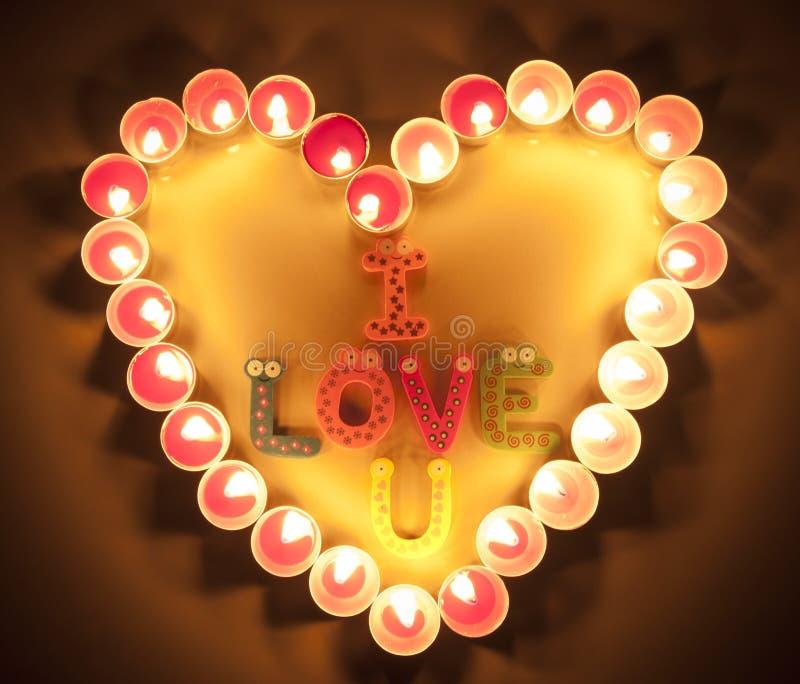Les bougies allument le coeur avec je t'aime des mots pour le fond romantique photo stock