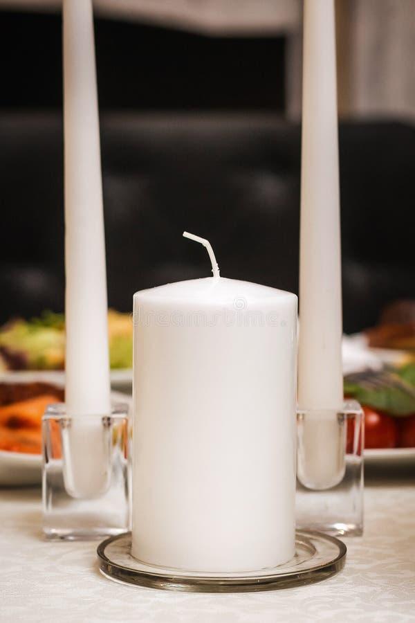 Les bougies se ferment vers le haut du standidng à la table de mariage image stock