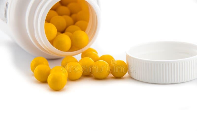 Les boules de dragée avec des vitamines ont dispersé à côté du récipient pour elles photographie stock libre de droits