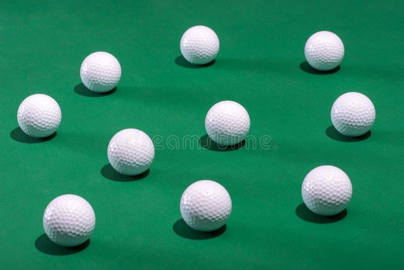 Les boules de golf blanches ont dispersé sur un tapis vert photographie stock libre de droits