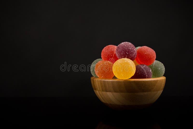 Les boules de gomme, fruit coloré Sugarcoated des boules de confiture d'oranges dans la cuvette en bois Sucrerie scandinave tradi image libre de droits