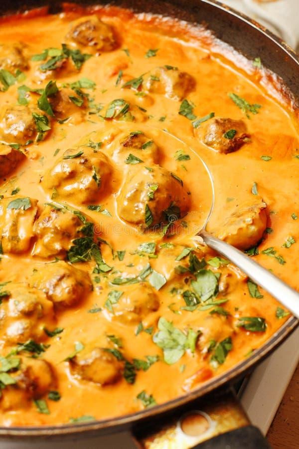 Les boules de poissons d'harengs en lait de tomate et de noix de coco sauce photo stock