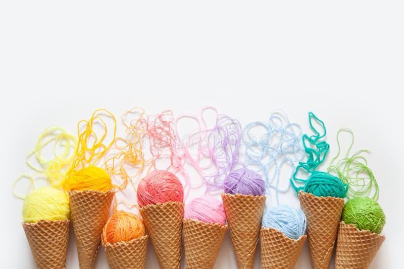Les boules du fil se situent dans un cône de gaufre pour la crème glacée  Laine colorée photographie stock libre de droits