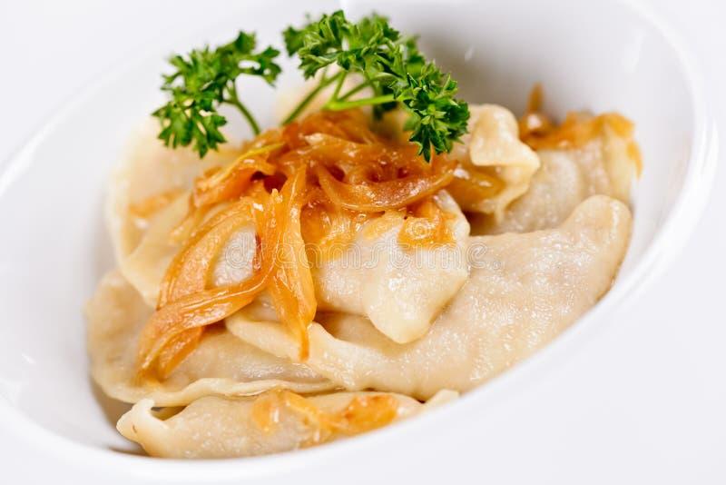 Les boulettes ont rempli de pomme de terre et ont complété avec l'oignon frit du plat blanc Varenyky, vareniki, pierogi photo libre de droits