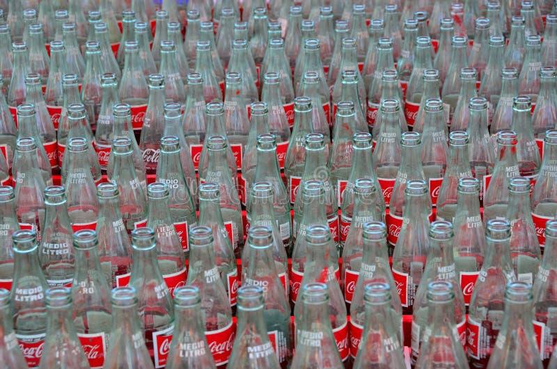 Les bouteilles de coke ont aligné pour le jet en l'air de boucle images stock