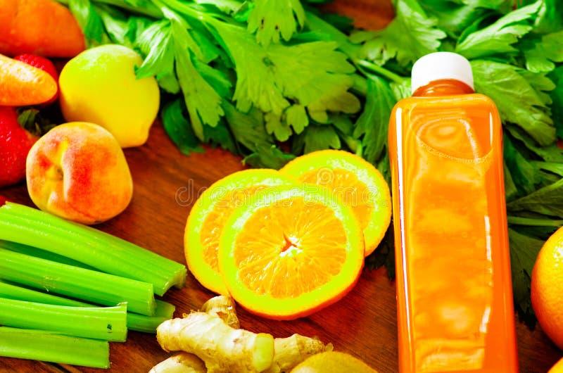 Les bouteilles de jus organique délicieux se trouvant sur le bureau sorrounded par des fruits et des veggies, belles couleurs, mo photo libre de droits