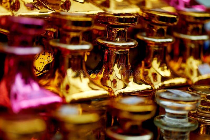 Les bouteilles de parfum en verre ont basé des huiles Un bazar, marché Macro Or et gamma rose photo stock