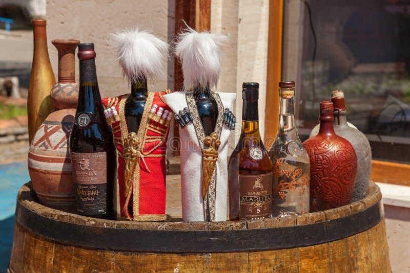 Les bouteilles de vin et de boissons alcoolisées se tenant sur les vieux barils sur la cour aménagent l'orientation en parc la Gé photographie stock