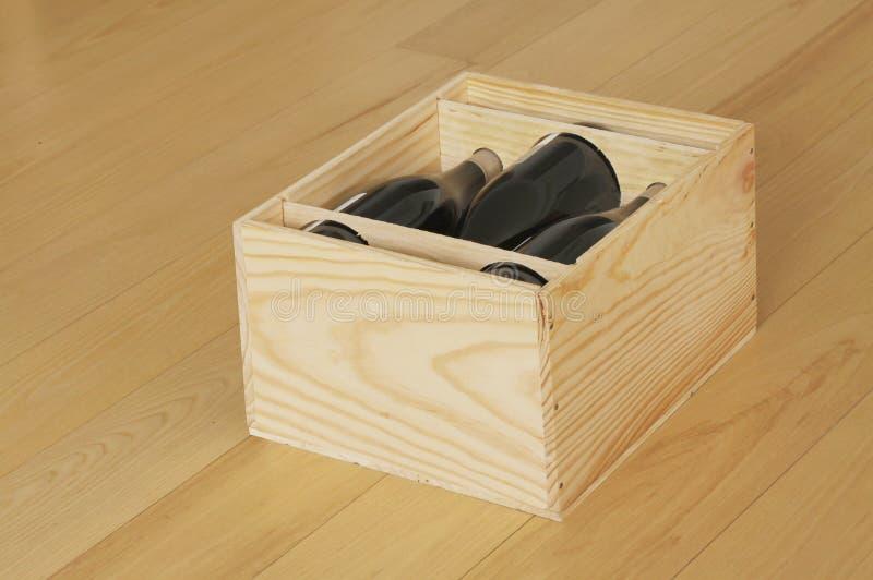Les bouteilles de vin rouge ont emballé dans la boîte en bois ouverte se tenant sur le plancher en bois images libres de droits