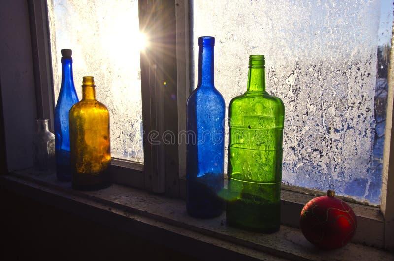 Les bouteilles en verre colorées sur la vieille fenêtre de ferme d'hiver avec la gelée glacent images stock