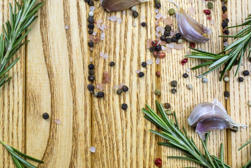 Les branches du romarin, ail, épices se trouvent sur un fond brun clair photographie stock libre de droits