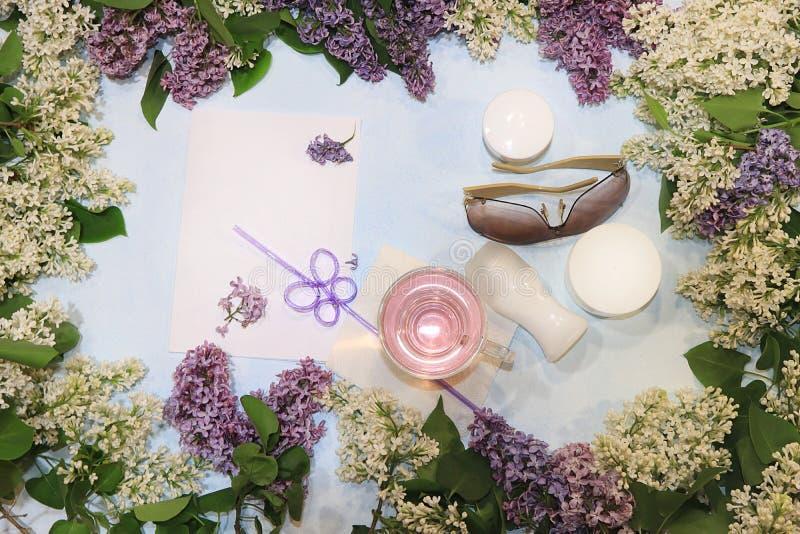 Les branches lilas colorées sur un fond bleu avec du jus, soins de la peau écrème, désodorisant et verres, configuration plate photos stock