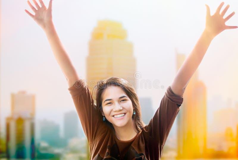 Les bras de l'adolescence biracial heureux de fille ont augmenté, des skyscapers à l'arrière-plan images stock