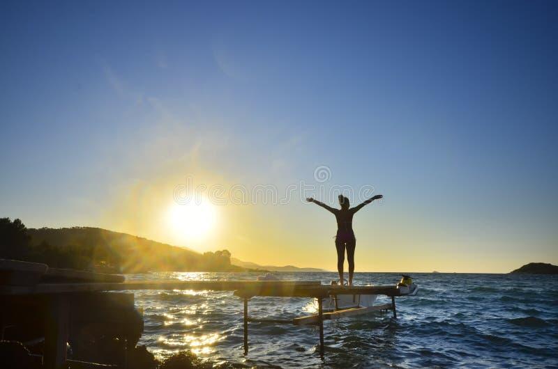 Les bras debout de femme heureuse tendus de retour et apprécient la vie sur le pilier de plage au coucher du soleil photographie stock libre de droits