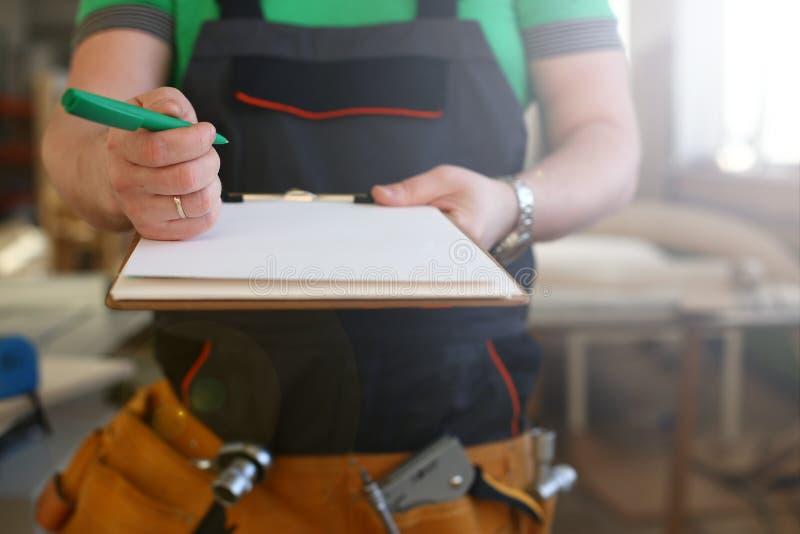 Les bras du travailleur offrent le presse-papiers avec le stylo vert photographie stock
