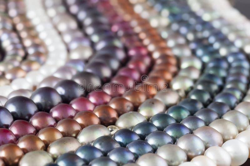 Les brins multicolores de perle en parallèle ondule la composition rétro-éclairée image stock