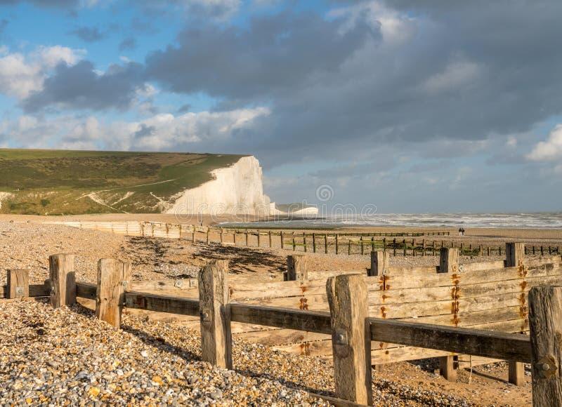 Les brise-lames en bois encadrent les falaises blanches de sept soeurs photos stock