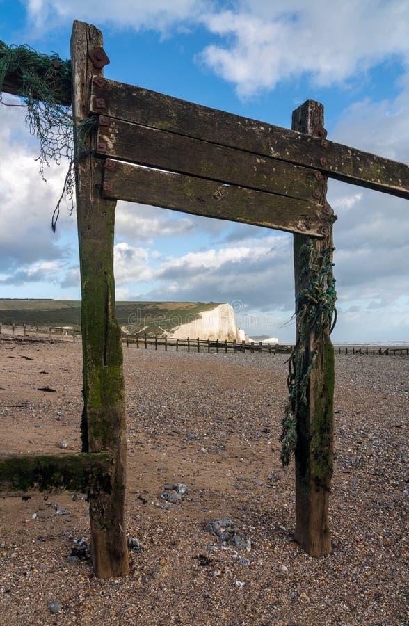 Les brise-lames en bois encadrent les falaises blanches de sept soeurs photos libres de droits