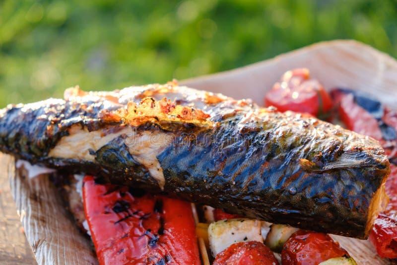 Les brochettes et les poissons végétaux grillés du maquereau dans une marinade d'herbe d'un plat, oignon, tomate de courgette de  images libres de droits