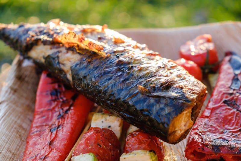 Les brochettes et les poissons végétaux grillés du maquereau dans une marinade d'herbe d'un plat, oignon, tomate de courgette de  image stock