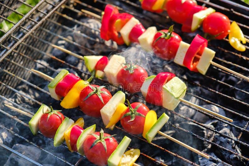 Les brochettes végétales grillées dans une marinade d'herbe sur une casserole de gril, tomate de courgette de poivre d'oignon ont image stock