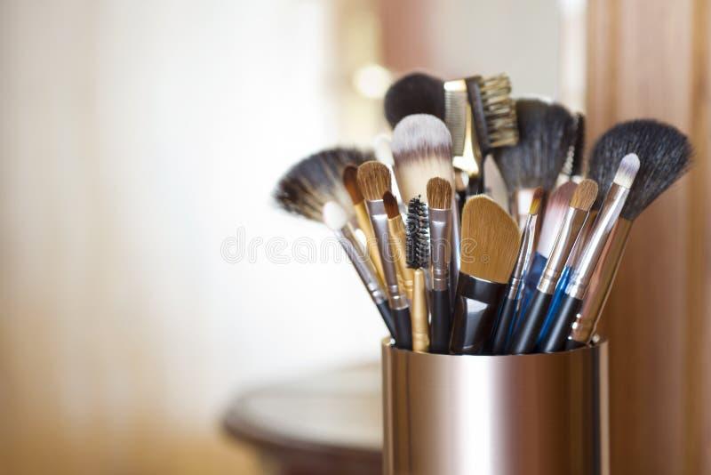 Les brosses de maquillage en métal se tiennent au-dessus du fond abstrait brouillé de pièce images stock