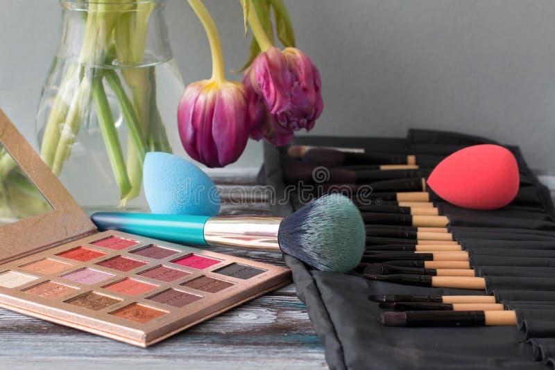 Les brosses, les ombres et les éponges cosmétiques professionnelles se trouvent sur une table en bois images stock